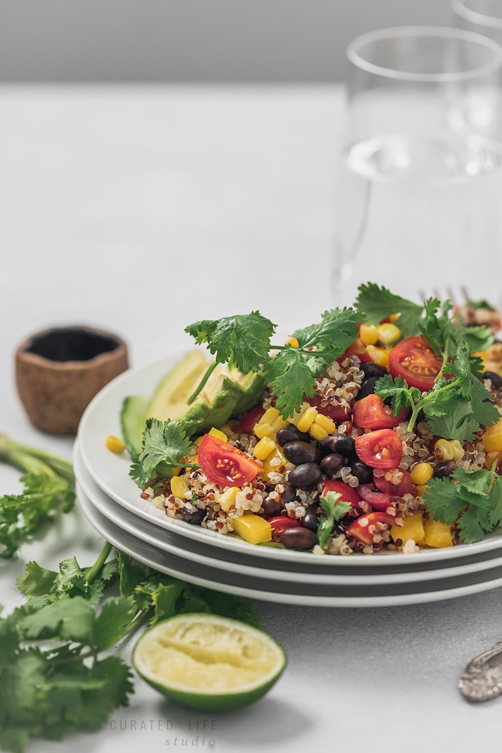 Black Bean Salad surrounded by other plates, creating a festive atmosphere.  (Curated Life Studio)  #quinoa #recipes #avocado #mexican #southwestern #healthy #easy #salad #black-bean #corn #vegan #gluten-free